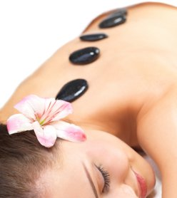 Smiling female face - Hot stone massage in the day spa - Portrait of a beautiful young girl at the day spa with black stones on her bare back